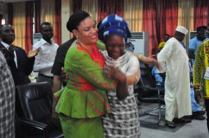 Bello Olabisi student from Dansol High School, Lagos, Winner of Children's Essay Writing Competition at NAFEST 2016 in a warm embrace with Mrs. Dayo Keshi, DG National Council for Arts and Culture