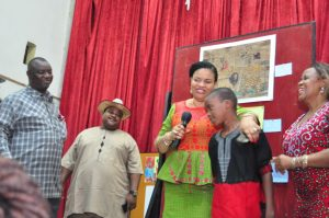 Abdulrahaman Saheed 13 years old student from Isolo Comprehensive High School, Lagos, Winner of Children's Drawing/Painting Competition at NAFEST 2016 been congratulated by Mrs. Dayo Keshi, DG, National Council for Arts and Culture while the Hon. Commissioner of Culture and Tourism Akwa Ibom State Hon. Otuekong Ibiok looks on